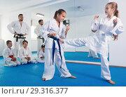 Купить «Pair of little girls practicing new karate moves during class», фото № 29316377, снято 25 марта 2017 г. (c) Яков Филимонов / Фотобанк Лори