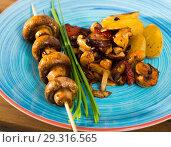 Купить «Tasty different mushrooms frying with potatoes at plate at table», фото № 29316565, снято 18 июня 2019 г. (c) Яков Филимонов / Фотобанк Лори