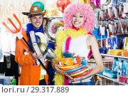 Купить «Smiling couple preparing to fest at accessories shop», фото № 29317889, снято 11 апреля 2017 г. (c) Яков Филимонов / Фотобанк Лори
