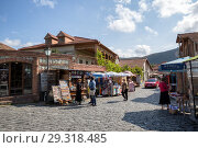 Купить «Tourists buy souvenirs on the street of the old town of Mtskheta near Svetitskhoveli Cathedral», фото № 29318485, снято 23 сентября 2018 г. (c) Юлия Бабкина / Фотобанк Лори