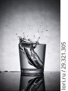 Купить «Water is splashing in glass cup standing on table», фото № 29321305, снято 2 января 2017 г. (c) Pavel Biryukov / Фотобанк Лори