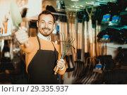 Купить «Seller displaying various items in garden equipment shop», фото № 29335937, снято 2 марта 2017 г. (c) Яков Филимонов / Фотобанк Лори