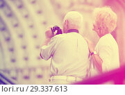 Купить «Back view of senior couple travellers making photo with camera», фото № 29337613, снято 16 декабря 2018 г. (c) Яков Филимонов / Фотобанк Лори