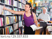 Купить «Teenage female is choosing interesting book», фото № 29337833, снято 28 июня 2017 г. (c) Яков Филимонов / Фотобанк Лори