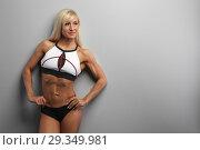 Купить «athletic beautiful blonde girl wears sportswear against a gray wall», фото № 29349981, снято 10 октября 2018 г. (c) Restyler Viacheslav / Фотобанк Лори