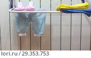 Купить «Женщина снимает детское белье с сушилки на радиаторе», видеоролик № 29353753, снято 1 ноября 2018 г. (c) Элина Гаревская / Фотобанк Лори