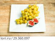 Купить «Fresh ripe figs and grapes in a bowl», фото № 29360097, снято 22 ноября 2019 г. (c) Игорь Бородин / Фотобанк Лори