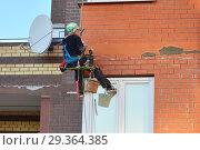 Промышленный альпинист осуществляет ремонт жилого здания (2018 год). Редакционное фото, фотограф Наталья Горкина / Фотобанк Лори