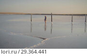 Купить «Slim sexy girl enjoying sunset, walks between wooden salt pillars of a salt lake», видеоролик № 29364441, снято 28 октября 2018 г. (c) Ирина Мойсеева / Фотобанк Лори