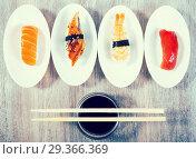 four kinds of Nigirisushi on saucers. Стоковое фото, фотограф Татьяна Яцевич / Фотобанк Лори