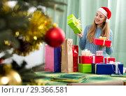 Купить «Young woman posing with Christmas gifts», фото № 29366581, снято 13 ноября 2018 г. (c) Яков Филимонов / Фотобанк Лори