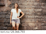 Купить «Young woman on old stone wall background», фото № 29366793, снято 15 августа 2017 г. (c) Яков Филимонов / Фотобанк Лори