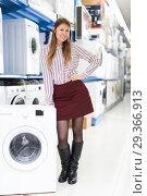 Купить «Female customer posing with washer in shop of electronics», фото № 29366913, снято 12 декабря 2017 г. (c) Яков Филимонов / Фотобанк Лори