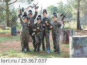 Купить «Friendly group of paintball players in camouflage standing with guns on paintball playing», фото № 29367037, снято 22 сентября 2018 г. (c) Яков Филимонов / Фотобанк Лори
