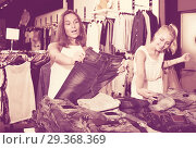 Купить «Two cheerful girls choosing denim trousers», фото № 29368369, снято 4 апреля 2020 г. (c) Яков Филимонов / Фотобанк Лори
