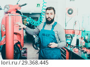 Купить «Positive male worker fixing failed motorbike», фото № 29368445, снято 25 июня 2019 г. (c) Яков Филимонов / Фотобанк Лори