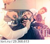 Купить «Male hairdresser accurately cutting beard of client», фото № 29368613, снято 27 января 2017 г. (c) Яков Филимонов / Фотобанк Лори