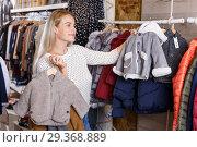 Купить «Woman showing baby costumes on hanger», фото № 29368889, снято 9 октября 2018 г. (c) Яков Филимонов / Фотобанк Лори