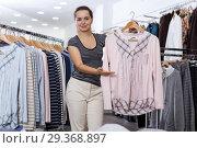 Купить «Woman holding and showing blouse on hanger», фото № 29368897, снято 10 октября 2018 г. (c) Яков Филимонов / Фотобанк Лори
