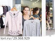 Купить «Woman demonstrating blouse on hanger», фото № 29368929, снято 10 октября 2018 г. (c) Яков Филимонов / Фотобанк Лори