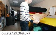 Купить «Sewing factory. A man taking templates from the wall. Close up», видеоролик № 29369377, снято 10 декабря 2018 г. (c) Константин Шишкин / Фотобанк Лори