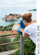 Купить «Observing place with coin operated telescope in the Sveti Stefan town. Woman looking at the same name island. Adriatic sea, Montenegro, Europa», фото № 29382845, снято 3 июня 2016 г. (c) Кекяляйнен Андрей / Фотобанк Лори
