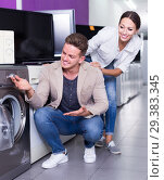 Купить «Young interested couple choosing washing machine in hypermarket», фото № 29383345, снято 18 ноября 2018 г. (c) Яков Филимонов / Фотобанк Лори