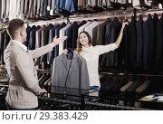 Купить «Female seller demonstrating numerous suits», фото № 29383429, снято 27 мая 2019 г. (c) Яков Филимонов / Фотобанк Лори