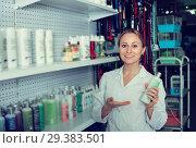 Купить «Cheerful female shop assistant offering shampoo», фото № 29383501, снято 15 ноября 2018 г. (c) Яков Филимонов / Фотобанк Лори