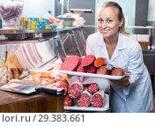 Купить «Positive young female picking tray with various salami», фото № 29383661, снято 19 января 2019 г. (c) Яков Филимонов / Фотобанк Лори