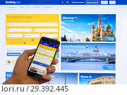 Adygea, Russia - January 16, 2018: The home page of the Internet booking of hotels booking.com on the screen the Chinese Xiaomi smartphone in male hand on a computer monitor. Редакционное фото, фотограф Андрей С / Фотобанк Лори