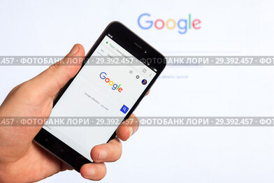 Adygea, Russia - January 4, 2018: the home page of popular web site the American search engine Google on the screen of the Chinese Xiaomi smart phone in male hand