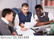 Three men are looking on documents and talking about it together. Стоковое фото, фотограф Яков Филимонов / Фотобанк Лори