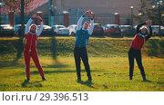 Купить «Two young woman and a man in sport costumes warming up in park», видеоролик № 29396513, снято 23 июля 2019 г. (c) Константин Шишкин / Фотобанк Лори