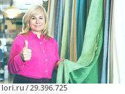 Купить «seller showing curtain and holding thumb up», фото № 29396725, снято 17 января 2018 г. (c) Яков Филимонов / Фотобанк Лори