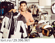 Купить «Man is demonstrating new jacket for motorbike in the store.», фото № 29396961, снято 1 сентября 2017 г. (c) Яков Филимонов / Фотобанк Лори