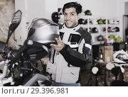 Купить «Male customer in new jacket is choosing modern helmet», фото № 29396981, снято 1 сентября 2017 г. (c) Яков Филимонов / Фотобанк Лори