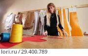 Купить «Young woman at sewing factory. A woman taking template from the wall.», видеоролик № 29400789, снято 10 декабря 2018 г. (c) Константин Шишкин / Фотобанк Лори