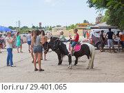 Купить «Мама фотографирует детей катающихся на пони по набережной имени Терешковой в курортном городе Евпатории, Крым», фото № 29401065, снято 1 июля 2018 г. (c) Николай Мухорин / Фотобанк Лори
