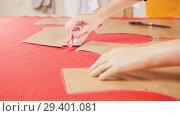 Купить «Young woman with arm prosthesis at sewing factory making sketches on the red cloth. Hands in focus», видеоролик № 29401081, снято 20 ноября 2018 г. (c) Константин Шишкин / Фотобанк Лори