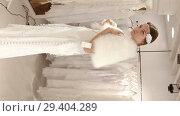 Young smiling woman flaunting dressed in wedding gown in wedding salon. Стоковое видео, видеограф Яков Филимонов / Фотобанк Лори