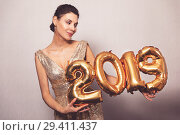 Купить «Happy New Year. Beautiful Woman with Balloons Celebrating new year's Eve Party. Smiling Girl in Bright Shiny Dress with 2019 Gold Number Balloons Fun At Celebration», фото № 29411437, снято 10 ноября 2018 г. (c) Сергей Тимофеев / Фотобанк Лори