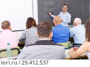 Купить «Confident lecturer talking to mixed age students», фото № 29412537, снято 28 июня 2018 г. (c) Яков Филимонов / Фотобанк Лори