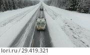 Купить «Движение грузовых и легковых автомобилей по зимней северной трассе, полет над машинами», видеоролик № 29419321, снято 12 ноября 2018 г. (c) Кекяляйнен Андрей / Фотобанк Лори