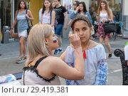 Купить «Девушка рисует флаг на щеке девочки. Москва, улица Никольская», эксклюзивное фото № 29419381, снято 2 июля 2018 г. (c) Alexei Tavix / Фотобанк Лори