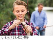 Купить «teenager boy holding catch fish on hook», фото № 29420489, снято 21 января 2019 г. (c) Яков Филимонов / Фотобанк Лори