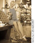 Купить «Happy young girl customer demonstrating sandals», фото № 29420897, снято 15 декабря 2018 г. (c) Яков Филимонов / Фотобанк Лори