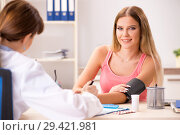 Young beautiful woman visiting doctor for blood pressure. Стоковое фото, фотограф Elnur / Фотобанк Лори