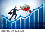 Купить «Businessman pushing wheelbarrow full of dollar money», фото № 29423321, снято 23 апреля 2019 г. (c) Elnur / Фотобанк Лори