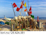 Local fishing boat surrounded by fishing floats on the beach at Monte Gordo, Algarve, Portugal in the evening sun. Стоковое фото, фотограф Findlay Rankin / age Fotostock / Фотобанк Лори